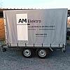 AM Elekro - aanhangwagen - Een aanhangwagen met bache voorzien van kleefletters in wit en zwart.